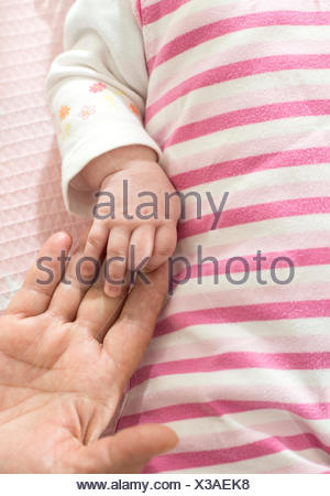 Woman's hand holding hand of baby girl - Stock Photo