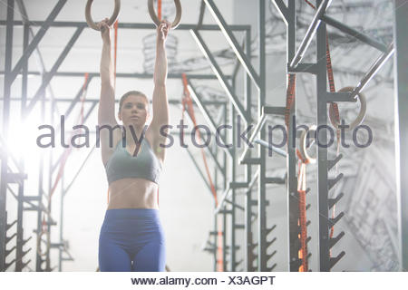 Confident woman exercising with gymnastic rings in crossfit gym - Stock Photo