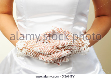 Mid section view of a bride wearing a pair of formal gloves