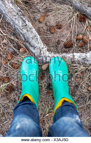 Close-up of woman in wellington boots standing in forest - Stock Photo