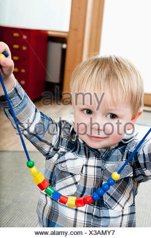 Proud little boy showing selfmade wooden perl necklace - Stock Photo