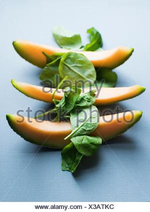 Three slices of fresh melon and spinach - Stock Photo