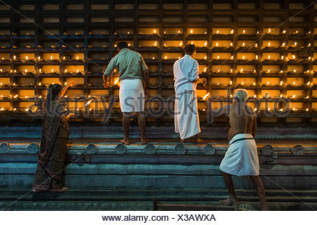 Oil lamps being lit in niches on the outer wall of the temple for the Hindu fire ceremony Aarti, Ambalapuzha, Kerala, India - Stock Photo