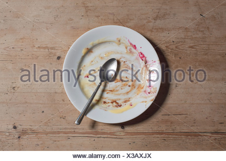Remains of eaten pudding on plate - Stock Photo