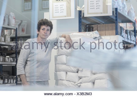 Portrait of female miller and flour sacks in wheat mill stockroom - Stock Photo