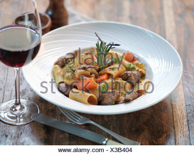 Paccheri pasta with slow cooked ox cheek, fresh rosemary, garlic, bay leaves, tomato and red wine - Stock Photo