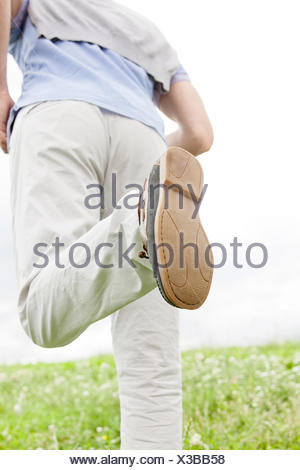 Cropped image of man running in park - Stock Photo