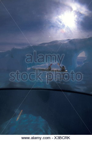 A view of kayakers passing by an iceberg that protrudes deep into the sea. The west coast of Antarctica's peninsula known as Gra - Stock Photo
