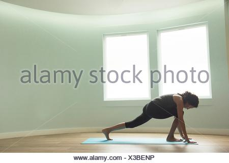 Mature woman practicing yoga in curved room - Stock Photo