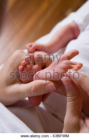 Woman holding her baby's legs - Stock Photo