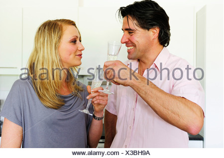 Young couple clinking glasses with champagne - Stock Photo