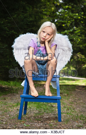 Bored girl in wings sitting on stool - Stock Photo
