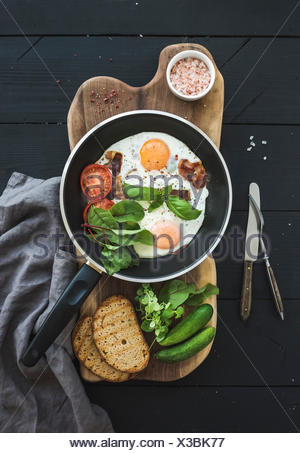 Pan of fried eggs, bacon, cherry tomatoes and fresh herbs with bread on wooden board over dark wooden background, top view - Stock Photo