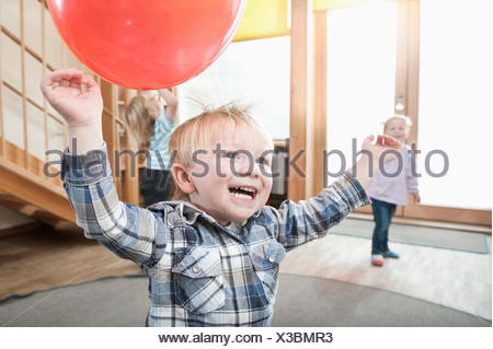 Kids playing with red balloons in kindergarten - Stock Photo