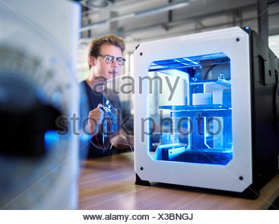 Employee, 25-30 years, opening 3D printer in production laboratory, FabLab, Wattens, Tyrol, Austria - Stock Photo