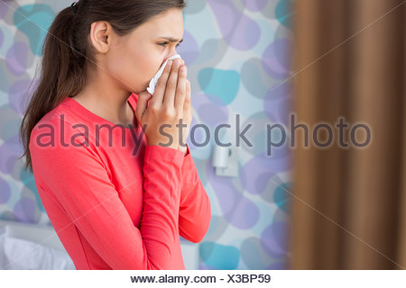Side view of young woman blowing nose at home - Stock Photo