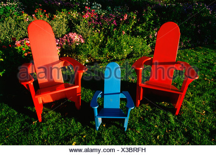 These are colored wooden lawn chairs. There are two large red chairs and one small blue chair in between two large ones. They - Stock Photo