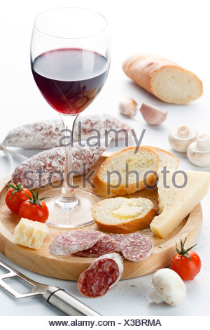 Wineglass with red wine and assortment of cheese and fruits on white background - Stock Photo