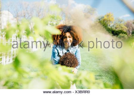 View through foliage of mother hugging daughter smiling - Stock Photo