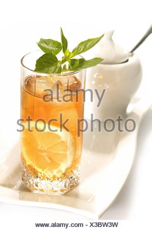 Cold black tea with lemon, ice and water drops on the glass surface - Stock Photo