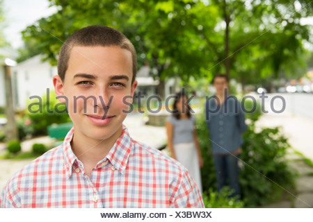 A boy on the farm, with two adults standing in the background. - Stock Photo