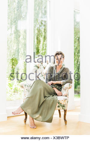 Portrait of senior woman sitting on armchair in living room - Stock Photo