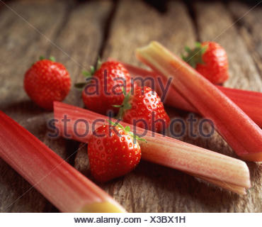 Strawberries and rhubarb on wooden table, close-up - Stock Photo