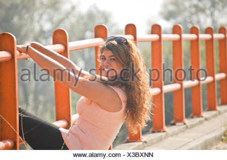 Long haired woman leaning on orange barrier and smiling to camera - Stock Photo