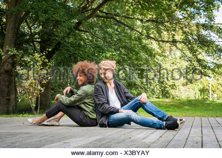 Sweden, Vastra Gotaland, Young smiling couple sitting on boardwalk in park - Stock Photo