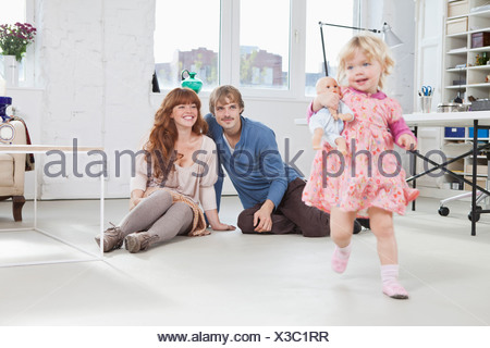 A young girl carrying a baby doll running around a living room - Stock Photo