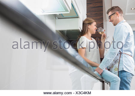 Affectionate couple in kitchen - Stock Photo