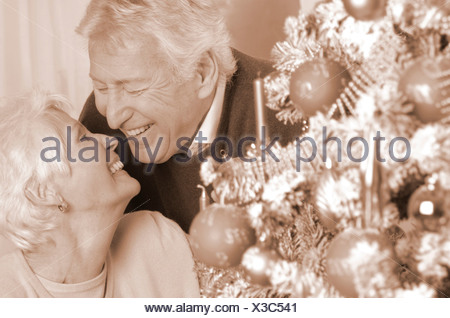 Mature couple looking lovingly at one another beside a Christmas tree - Stock Photo