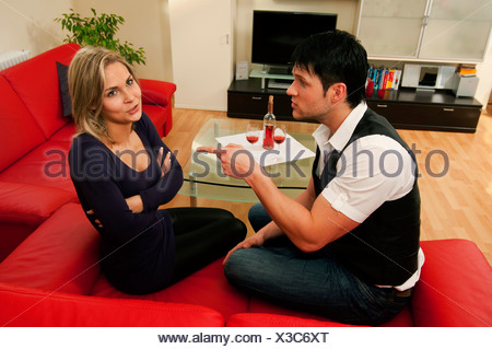 couple sitting on sofa and diskussing, Germany - Stock Photo