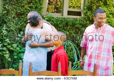 Couple hugging at family picnic - Stock Photo