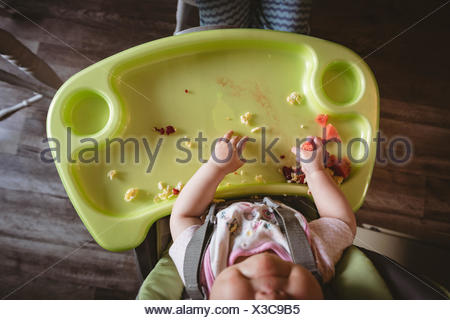 Overhead of baby sitting in high chair - Stock Photo