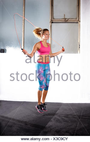 Young woman skipping in gym - Stock Photo