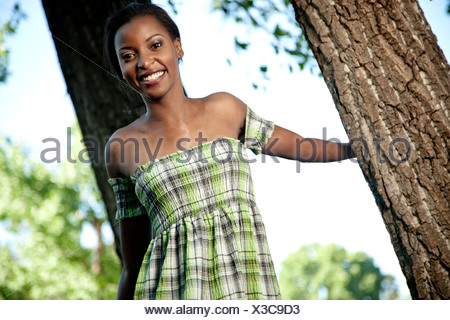 Young black lady leaning against a tree in a park, smiling at camera - Stock Photo