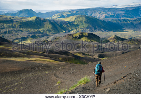 View towards Mýrdalsjoekull Glacier, hiker in the Black Lava Desert, with moss-covered mountains along the Laugavegur hiking - Stock Photo