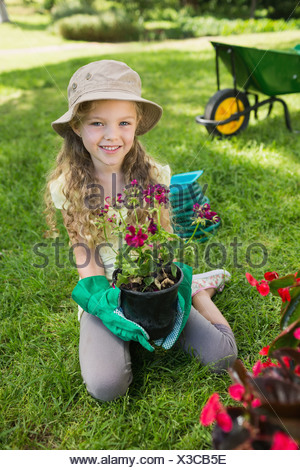 Smiling girl engaged in gardening - Stock Photo