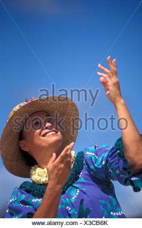 Close-Up Of Older Hawaiian Woman (Tutu) Dancing On Beach, Hands In Air - Stock Photo