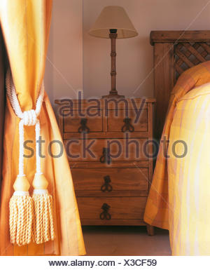 Yellow curtain with a silk rope tie-back in Spanish bedroom with a wooden chest-of-drawers beside the bed - Stock Photo