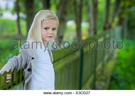Girl, 4 years old, leaning against a wooden fence - Stock Photo