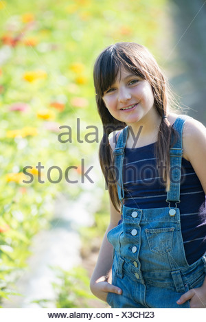 Summer on an organic farm. A young girl in a field of flowers. - Stock Photo
