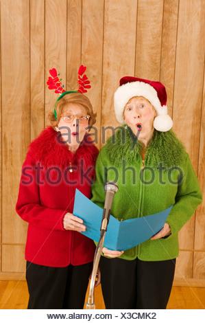 Elderly women singing at Christmastime - Stock Photo