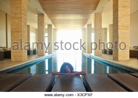 Portrait of young woman relaxing in spa swimming pool - Stock Photo