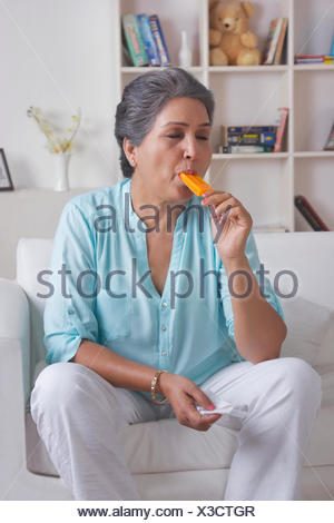 Old woman eating ice cream - Stock Photo