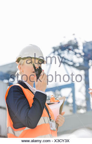 Female engineer using walkie-talkie in shipping yard - Stock Photo