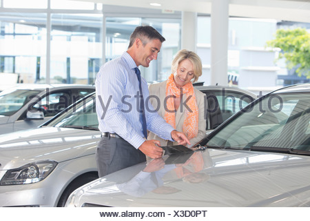 Salesman and customer looking at brochure in car dealership showroom - Stock Photo