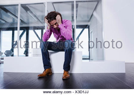 Mature man sitting on podium with head in hands - Stock Photo