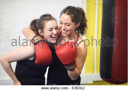 Two female boxing friends pretending to punch in gym - Stock Photo